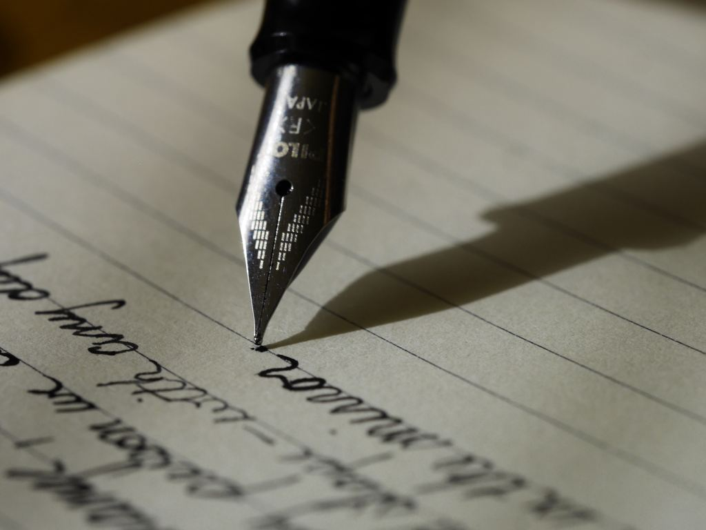 Image of a fountain pen being used to write on cream, lined paper.  Several lines of text are visible, and the pen has just written a full stop.